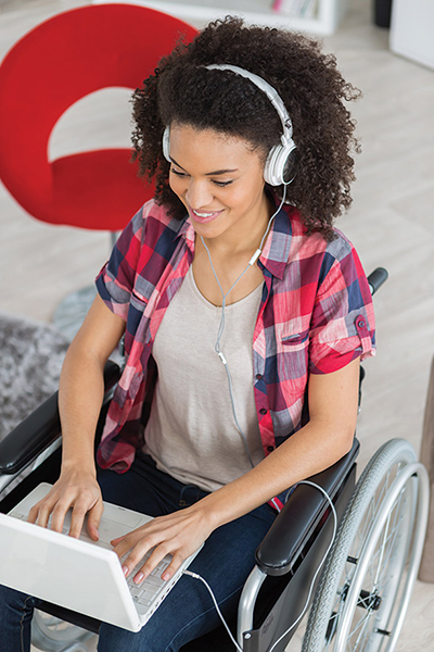 Student in wheelchair using a laptop.